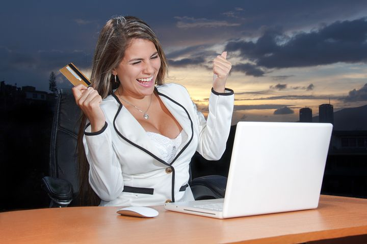 happy lady with credit card on a laptop